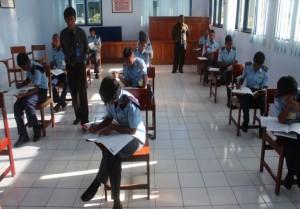 Peserta Ujian Nasional sedang mengerjakan soal Ujian Nasional yang didampingi oleh pengawas